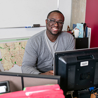 picture of Led young College Social Service Worker program alumni Stephen Linton smiling and sitting in his City of Toronto office