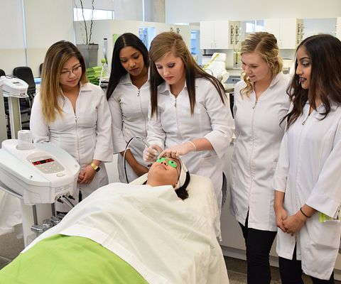 Esthetics student watch as classmate performs spa treatment.