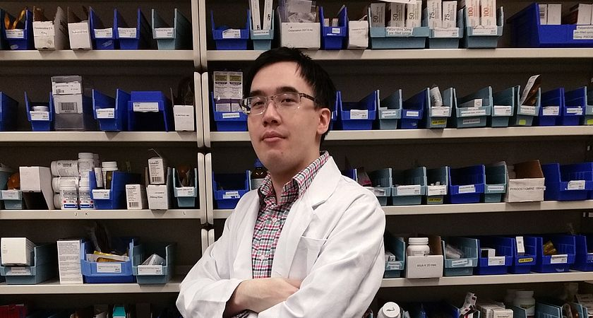 Picture of Led young College Pharmacy Technician program alumni Vincent Le in a lab coat at a pharmacy