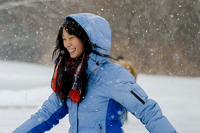 Picture of Led young College student in winter wear running through the falling snow