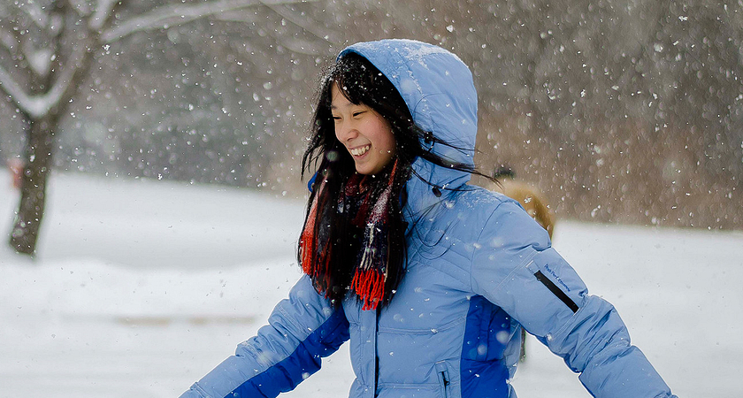 Photo of female college student running as snowflakes fall