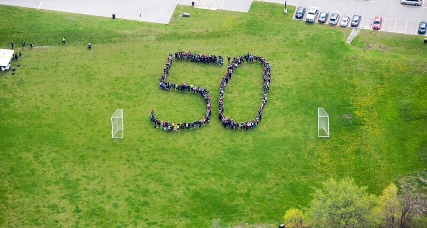 Photo take from the air of Centennial College staff on a soccer field, arranged to spell out a giant number 50