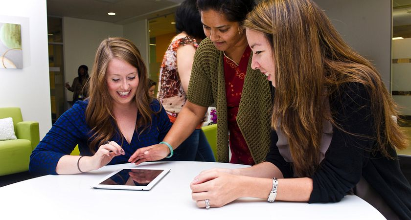 Three female COLT staff members look at a tablet on the table inside the Gathering Place at Progress campus