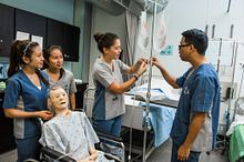 Picture of nursing students practicing hands on with medical equipment and a dummy in a hospital simulated training lab, as part of a community services and health program at Centennial College.