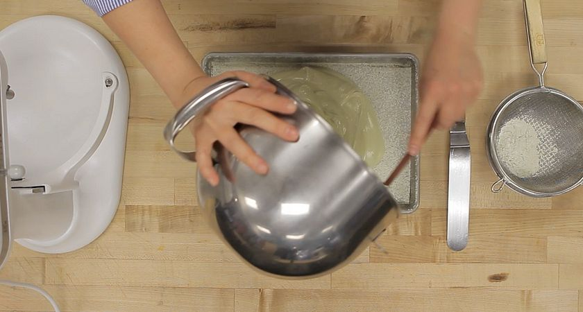 picture of hands pouring a marshmallow mixture from a bowl onto a tray