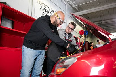 Two male automotive students looking under the hood of a red car in the auto repair shop