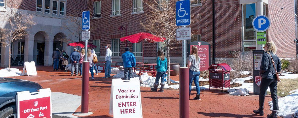 人们排队等待COVID-19疫苗