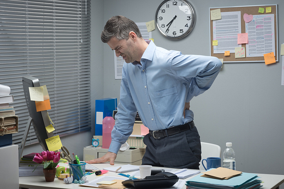 man with back pain at desk