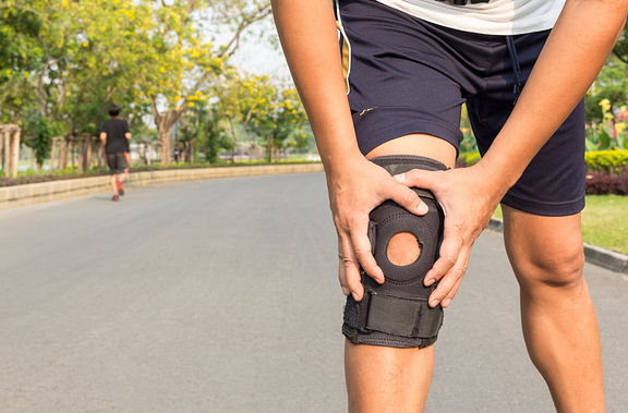 Runner wearing knee brace