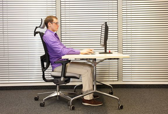man sitting in ergonomic chair at office desk