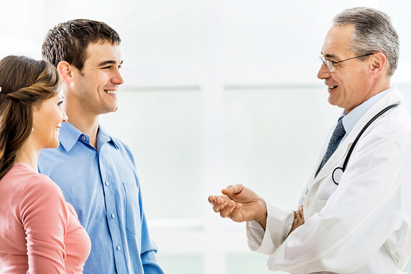 Doctor talking to young couple