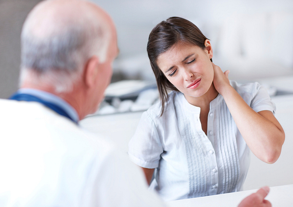 woman with neck pain at doctor consultation