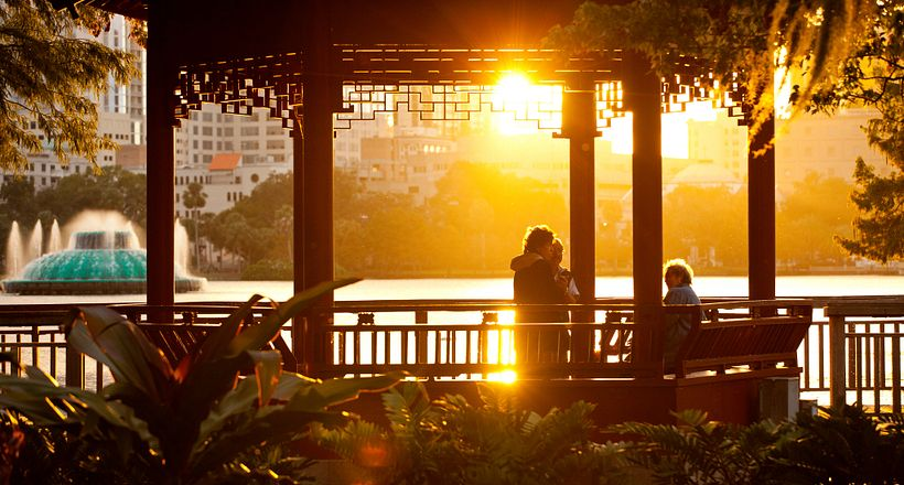 A small group enjoy the sunset from within the Chinese pavilion, or ting, near the water's edge at Lake Eola in downtown Orlando.