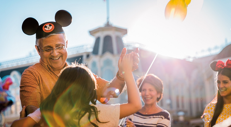 Grandfather with Mickey Mouse ears dancing on Main Street with his grand-daughter.