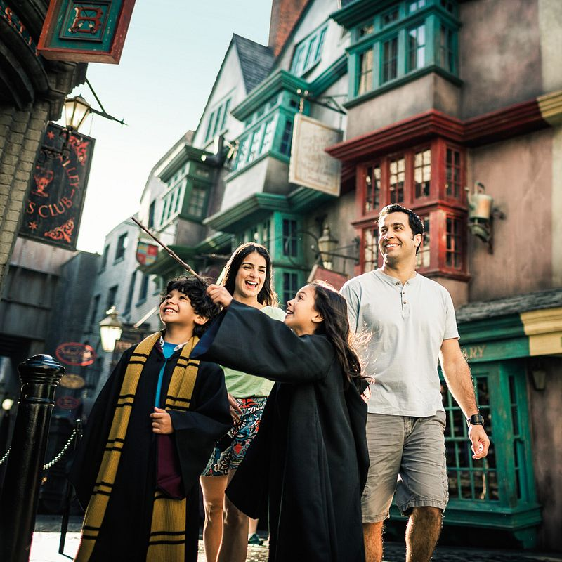 Girl casting a spell with her family in Diagon Alley at Universal Studios Florida.