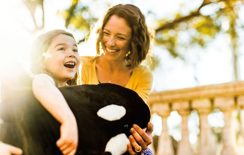 Mother with young daughter holding a Shamu plush toy