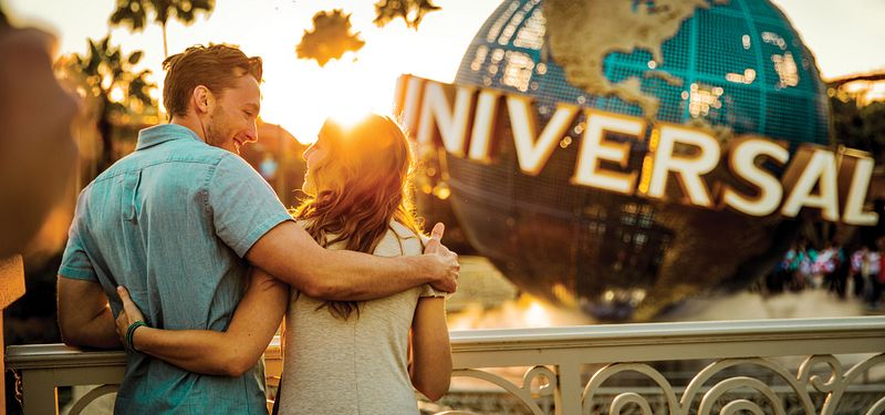 Couple at sunset in front of the globe at Universal Studios Florida.