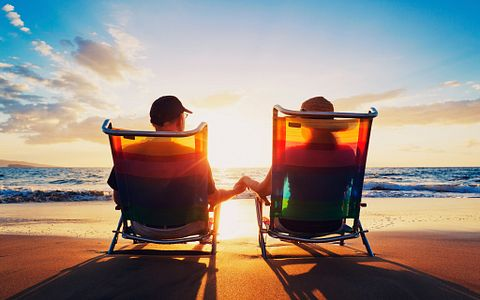 Couple holding hands while enjoying a beautiful sunrise on the beach