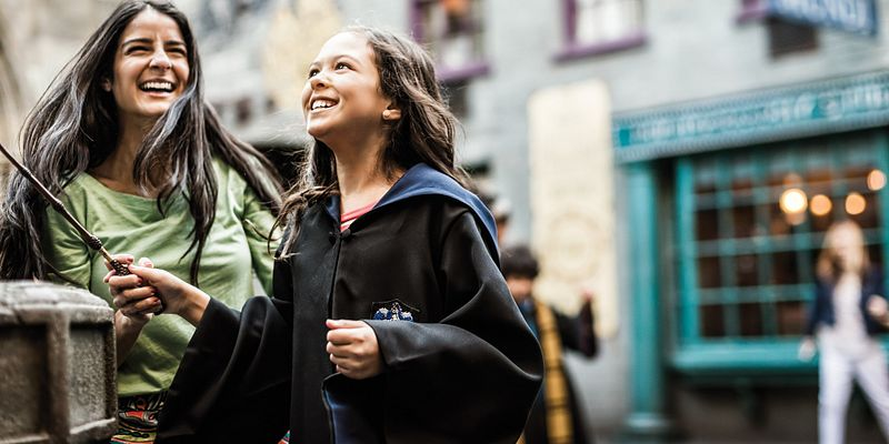 Mother and daughter with magic wand having fun in Diagon Alley at Universal Studios Florida.