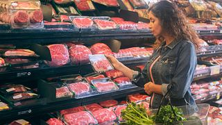 Woman shopping at the open meat case