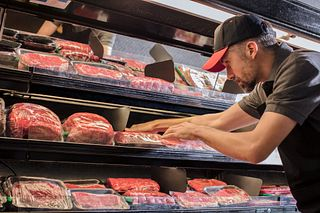 Butcher stocking meat case