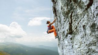 Young slim female rock climber climbing on the cliff