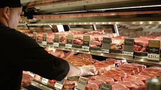 butcher at meat case
