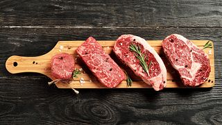 Fresh raw Prime Black Angus beef steaks on wooden board