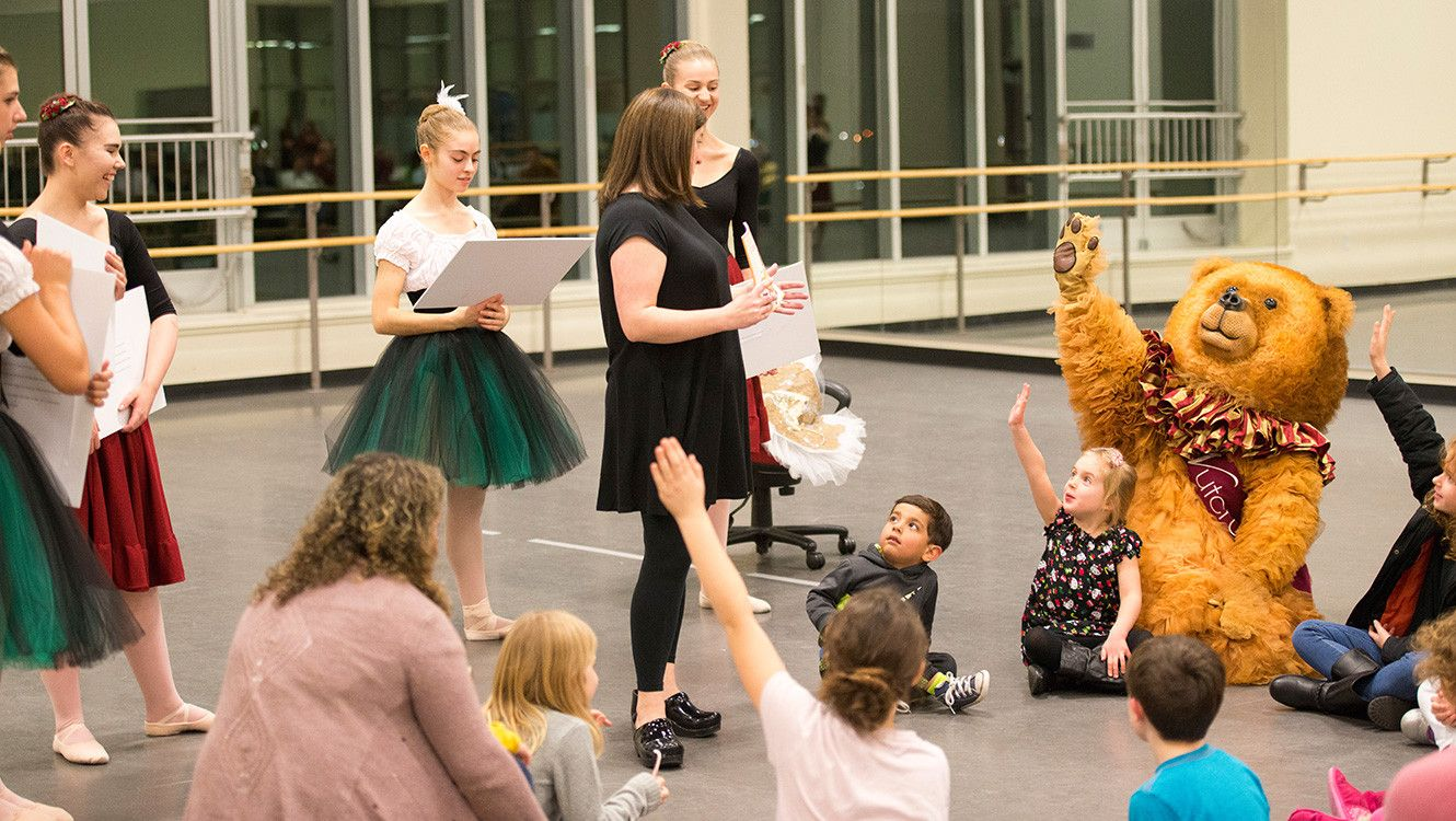 Image with a teacher and four young female assistants in long bright colored tutus telling a story to a group of young children and the Nutcracker Bear