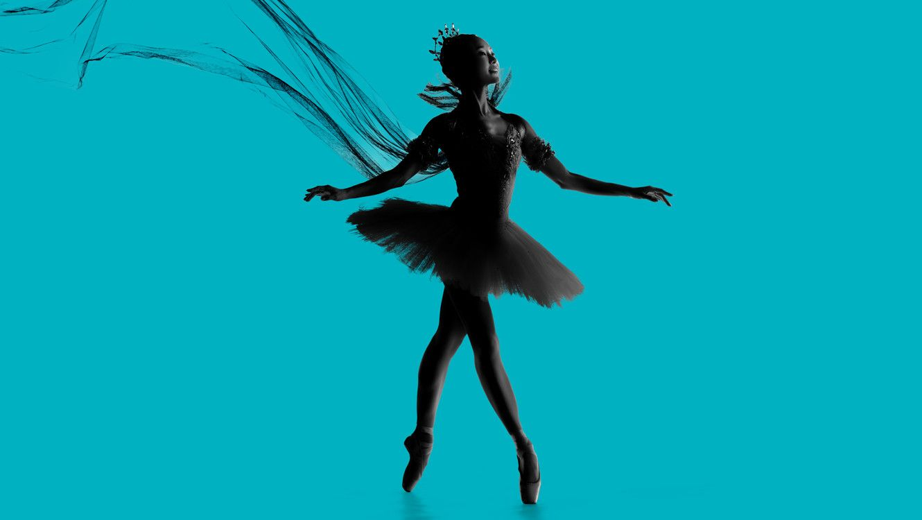 Image Seo Hye Han in tutu and cape on a light blue background. Photo by Rachel Neville Photography