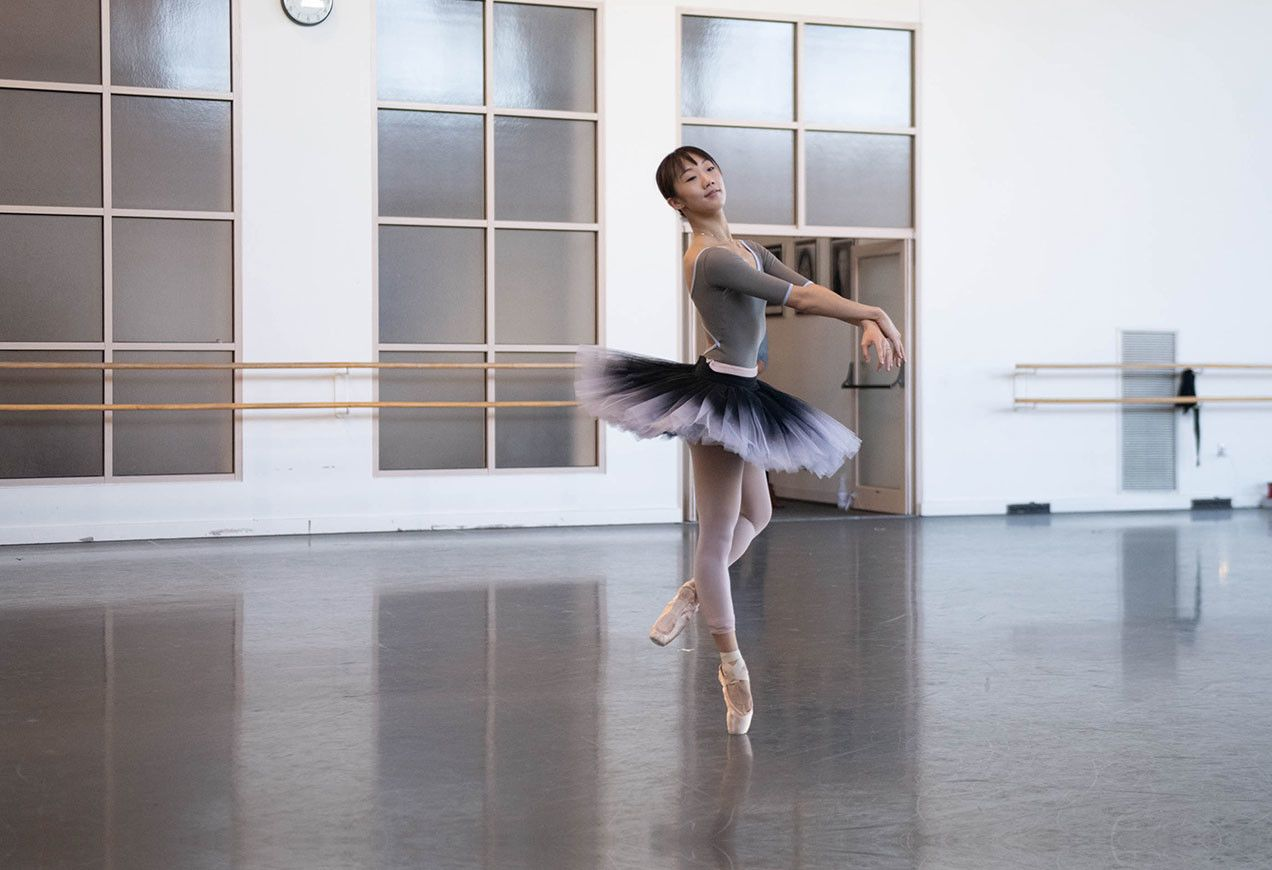 Chisako Oga in the studio wearing a grey leotard and black and grey tutu. Photo by Brooke Trisolini
