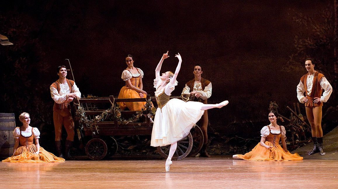 Larissa Ponomarenko as the character Giselle dancing in an arabesque in front of Artists of the Company from the ballet Giselle photographed by Gene Schiavone
