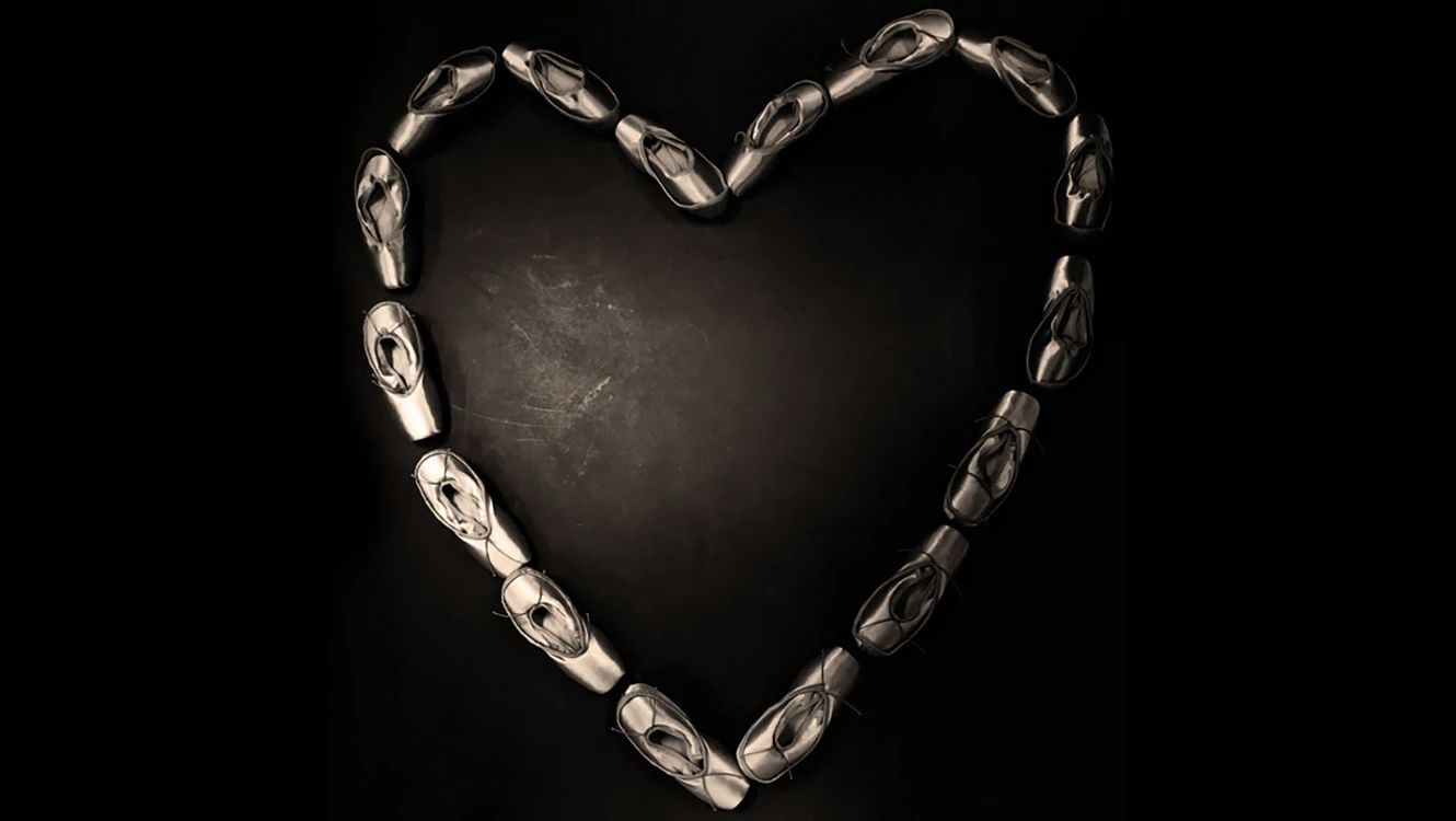silvered pointe shoes arranged in a heart shape against a black background.