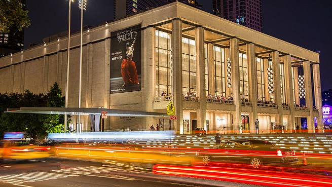 Hyper lapse image of cars outside of Lincoln Center. Building has a Boston Ballet image projected onto the side. Image links to the Boston Ballet On Tour Page