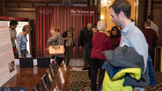 Male figure looks at framed images and descriptive poster board display on a table in the lower lobby of the Citizens Bank Opera House