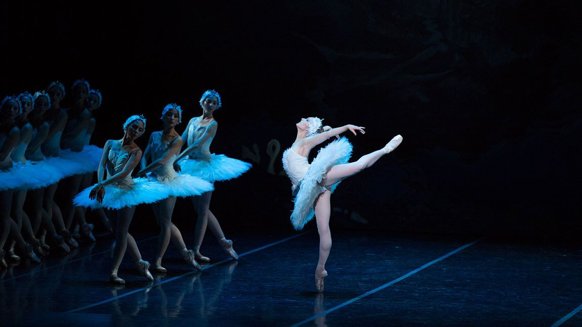 Image of ballerina Ashley Ellis in an arabesque with corps de ballet members posed to the left of the image. Photo by Rosalie O'Connor