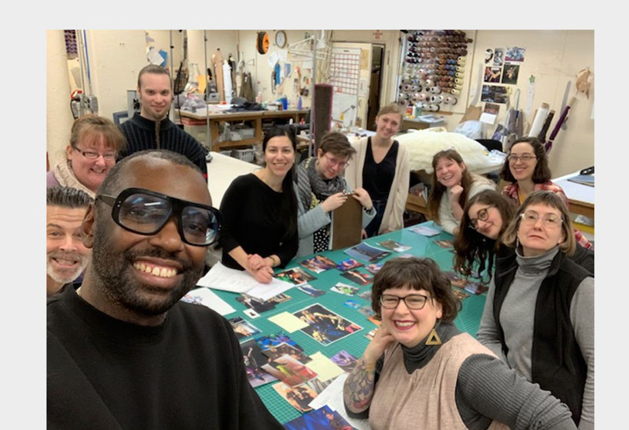 Stephen Galloway and costume shop staff in the Boston Ballet costume shop around a table with design ideas