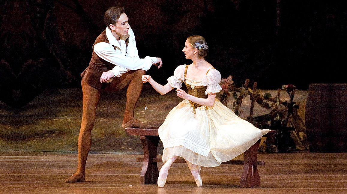 Larissa Ponomarenko as the character Giselle sitting on a bench with Roman Rykine as the character Albrecht standing next to the bench  from the ballet Giselle photographed by Gene Schiavone