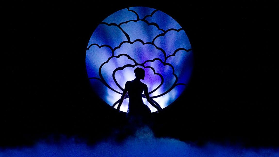 Dancer Lia Cirio silhouetted against a purple moon backdrop on stage in Helen Pickett's Tsukiyo. Photographed by Gene Schiavone