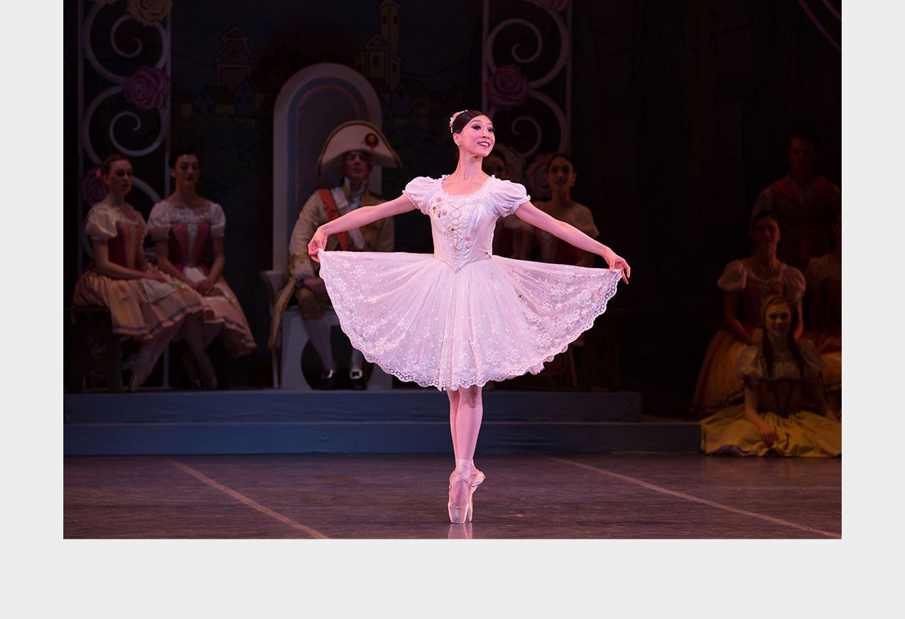 Misa Kuranaga on stage in George Balanchine's Coppelia. She stands holding her skirt out to each side.