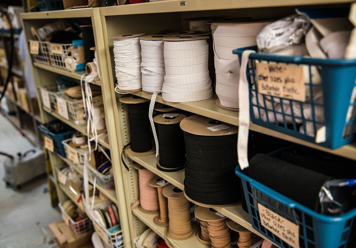 Image of shelves with spools of fabric tape, ribbons, and baskets of ribbon