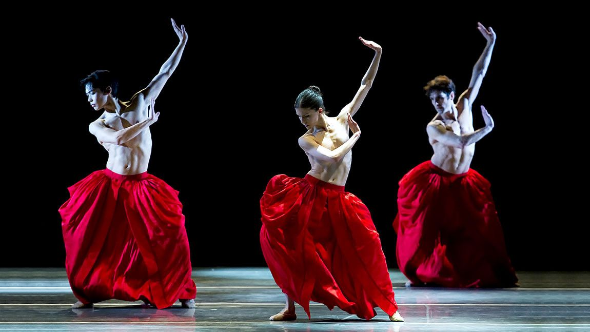 Sarah Wroth, Altan Dugaraa, and Yury Yanowsky onstage in large red skirts in Jiří Kylián's Bella Figura photographed by Gene Schiavone