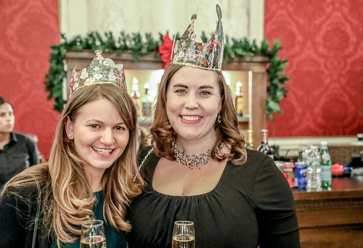 Two women in dark shirts Nutcracker crowns standing in front of the bar at Citizens Bank Opera House