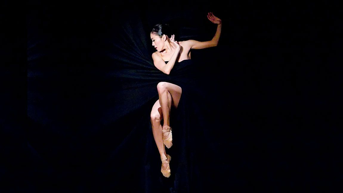 Dancer Rie Ichikawa wrapped in a black curtain in Jiří Kylián's Bella Figura, photographed by Gene Schiavone