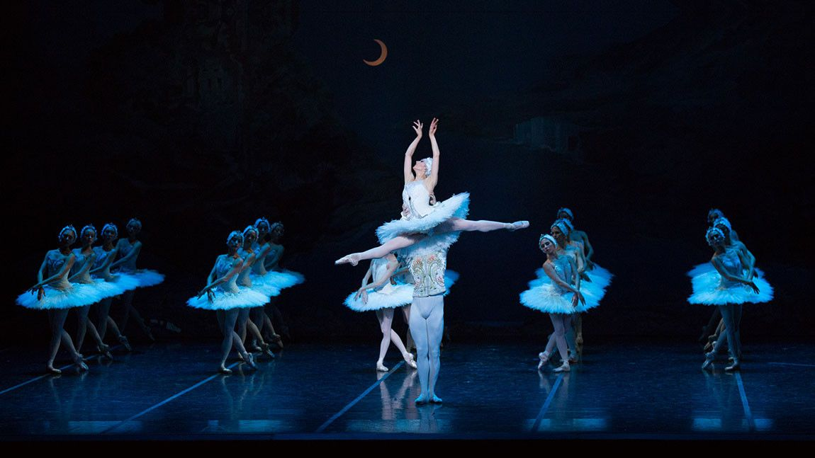 Image of Boston Ballet dancers on stage in Mikko Nissinen's Swan Lake. Ballerina Ashley Ellis is being lifted in a jump by a male dancer with corps de ballet dancers in the background. Photo by Rosalie O'Connor