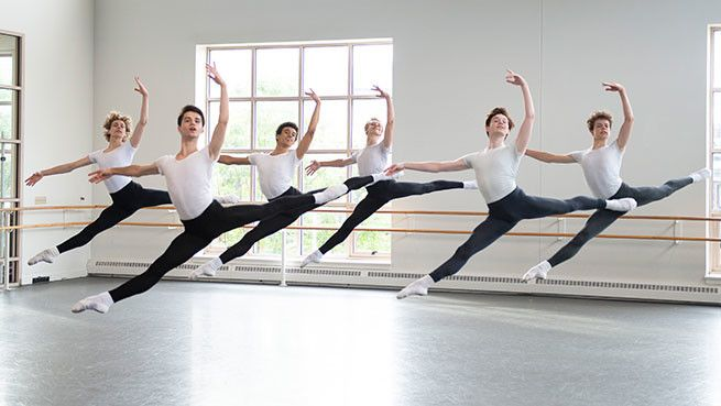 Male ballet students in leotards and tights leaping in a studio