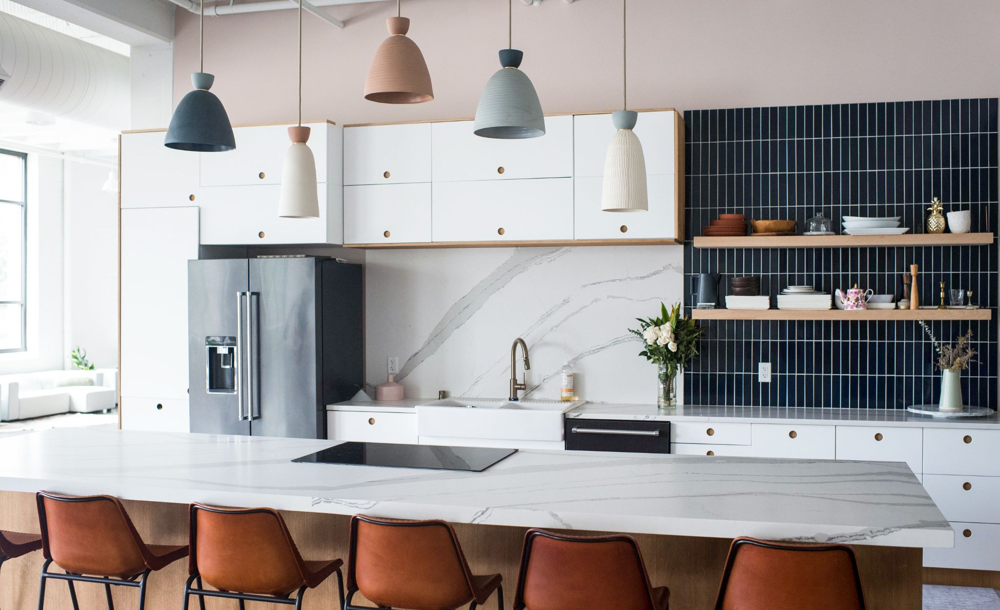 Striking design selections from Brittanicca Matte countertops and backsplash to navy Fireclay Tile and Rejuvenation ceramic pendants create a memorable kitchen focal point.