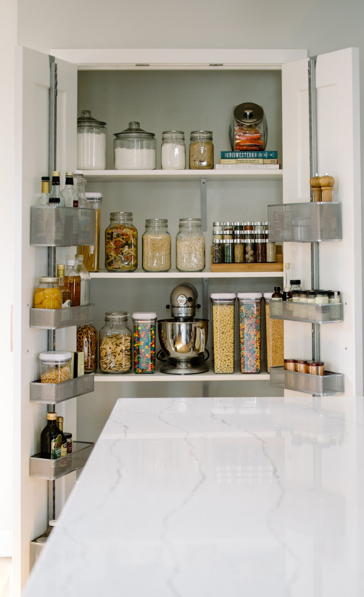 An organized kitchen pantry in a kitchen featuring Cambria Ella countertops.