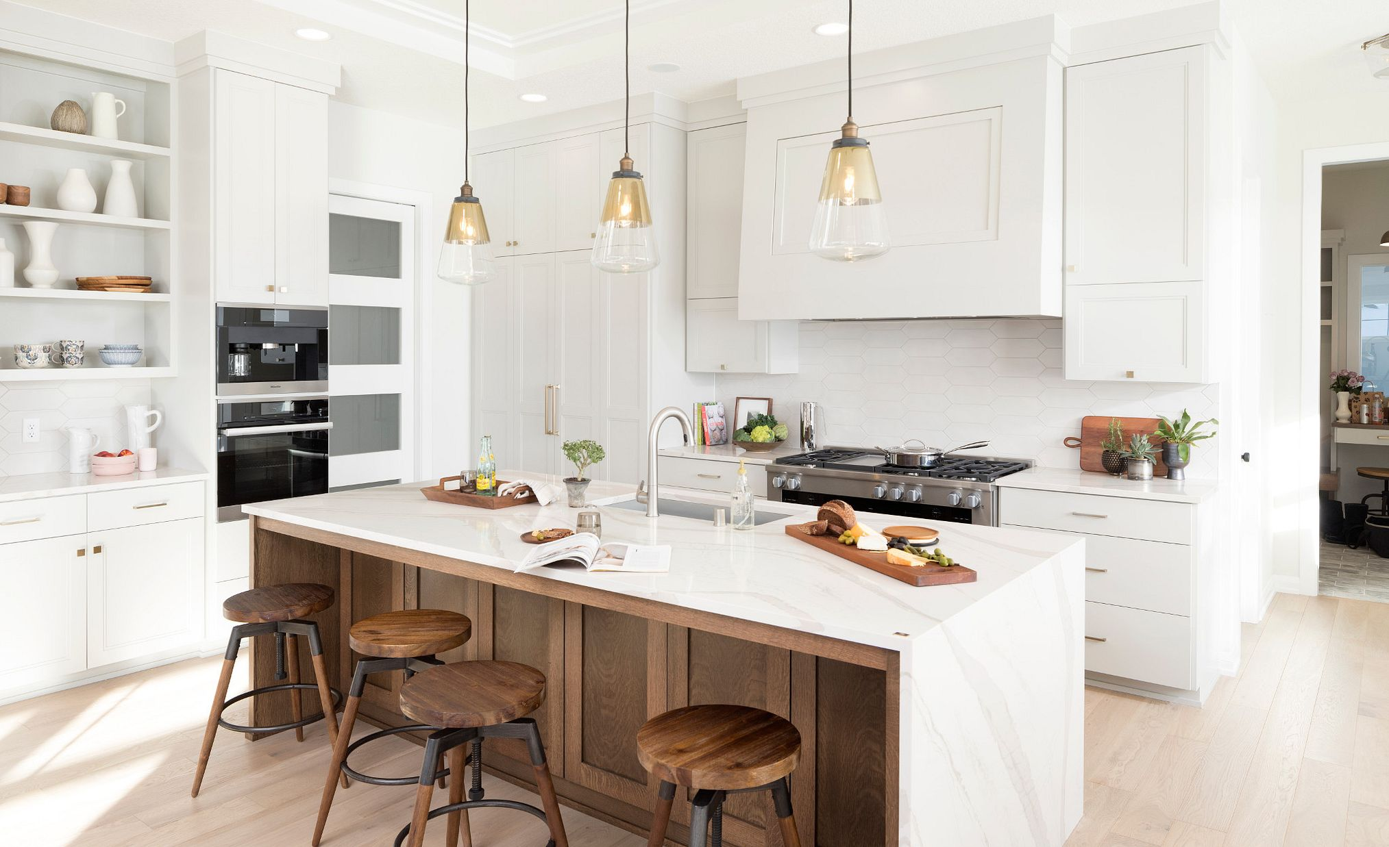 White marble-look quartz countertops in a kitchen with white and medium wood toned cabinets.