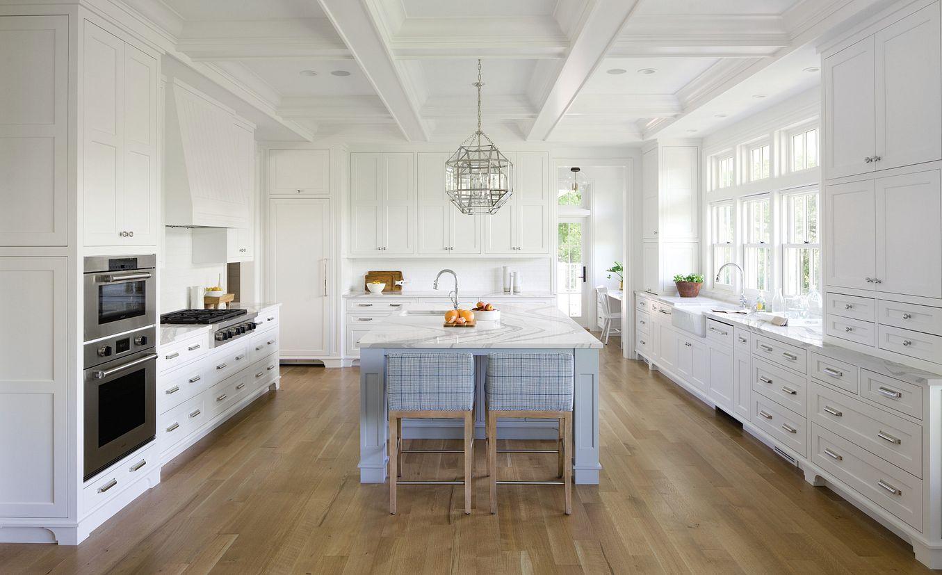 White kitchen with light blue-gray island and Cambria Brittanicca countertops.